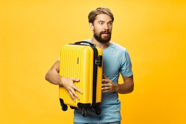 スタジオ、休暇でポーズをとって彼の手でスーツケースを持つ男性旅行者