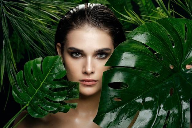 ヤシの茂み、顔の美しい肌の美しい女性の肖像画