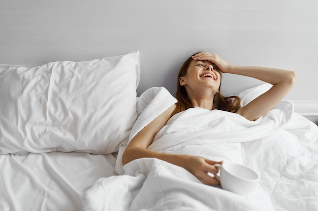 Красивая молодая женщина в своей красивой белоснежной кровати отдыхает и расслабляется, прекрасное свидетельство