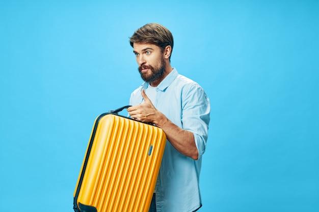 Мужской путешественник с чемоданом в руках позирует в студии, отпуск