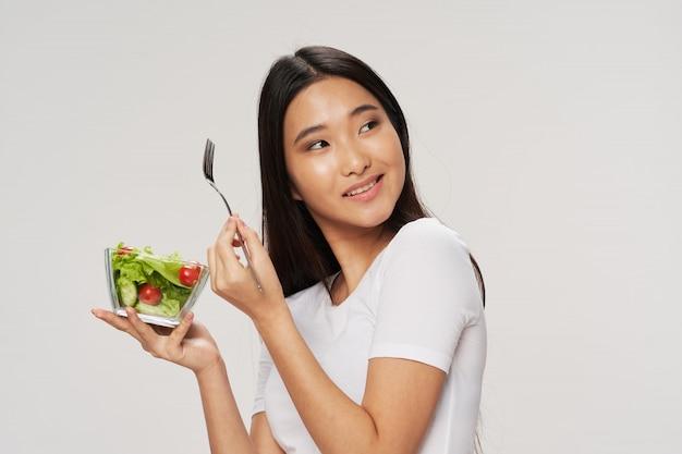 アジアの女性がサラダを食べる