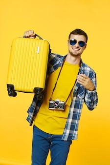 スーツケース、色付きの背景、喜び、パスポートを持つ男性旅行者