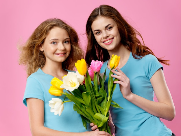 母の日、花とスタジオでポーズをとる子供を持つ若い女性、女性の日と母の日への贈り物