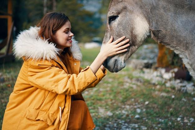Женщина позирует с ослом на природе в горах