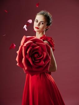 Красивая молодая женщина в роскошном платье с розами, лепестками роз, стильным образом, красной помадой