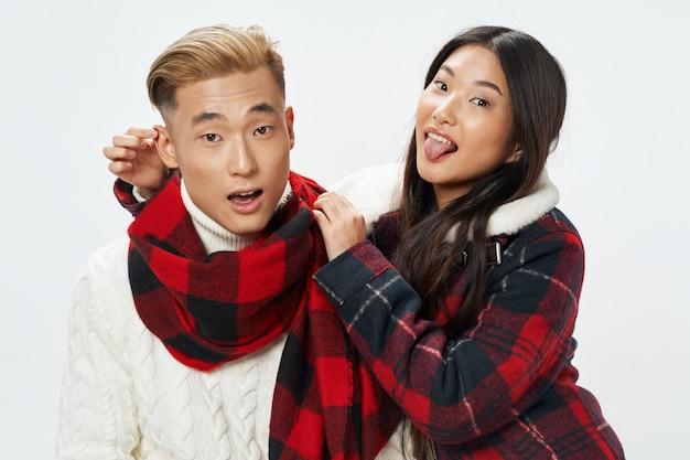 アジアの女性と一緒にモデルをポーズ明るい色の表面上の男
