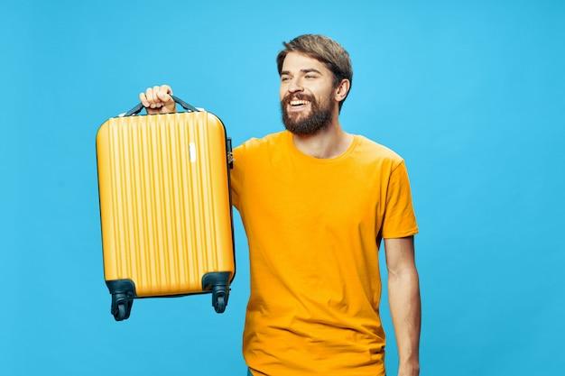 スタジオ、休暇でポーズをとって彼の手にスーツケースを持つ男性旅行者