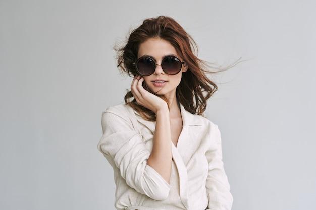 スタイリッシュなアクセサリーとファッションの服でポーズをとる若い美しい女性モデル