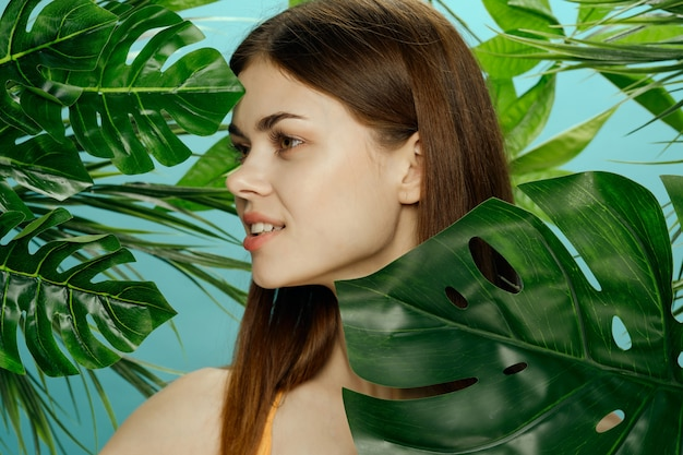 Красивый женский портрет в пальмовых кустах, красивая кожа лица