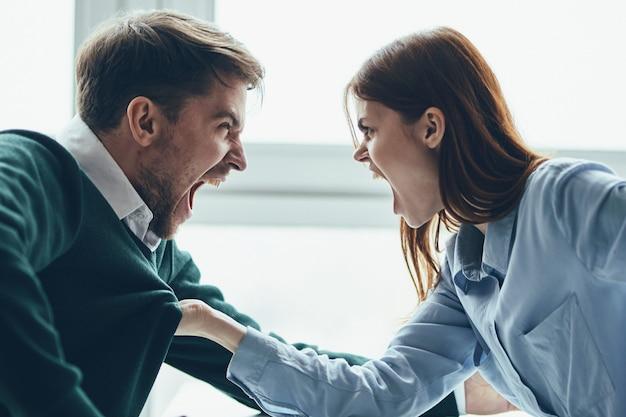 男と女がテーブルに座って話し、お互いに口論をしている、本当の口論、家事問題