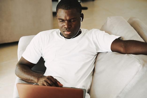 Афро-американский мужчина работает на дому фрилансера ноутбук