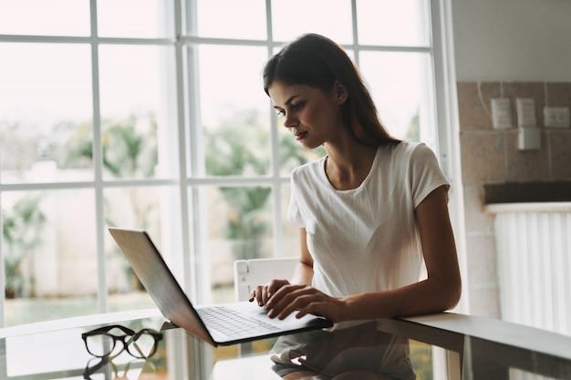テーブル作業と休憩でラップトップを持つ若い女性