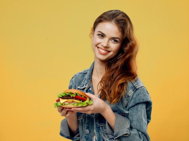 Красивая молодая женщина с сочным гамбургером в руках, женщина ест гамбургер