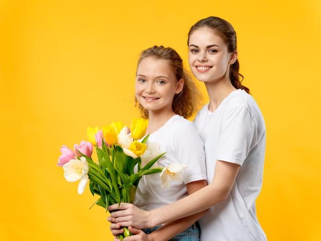 母の日、花のあるスタジオでポーズをとる子供を持つ若い女性、女性の日と母の日への贈り物