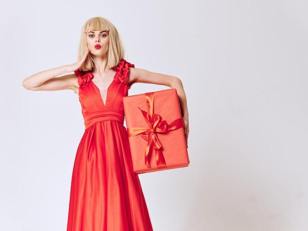 ギフト用の箱と美しいドレスの女性