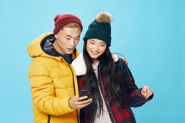 Азиатская женщина и мужчина на яркой цветной поверхности, создает модель вместе