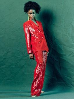 Женщина афроамериканец в блестящей праздничной модной одежды на цветной поверхности позирует