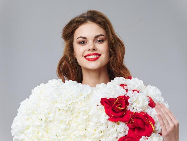 Весной молодая красивая девушка с цветами на цветном пространстве, женщина позирует с букетом цветов, женский день