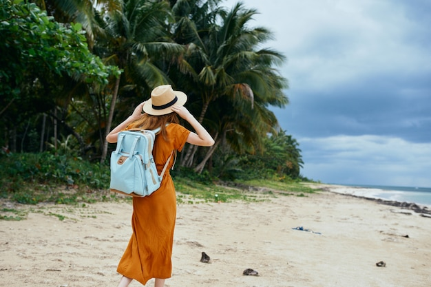 黄色のドレスと帽子の青いバックパックを持つ女性は、ヤシの木が付いている砂に沿って海に沿って歩く