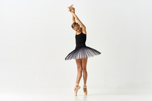 Женщина балерина танцует балет в студии