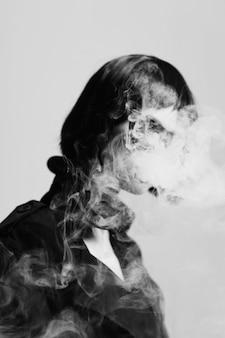 スタイリッシュなイメージを喫煙顔なしポーズの煙を持つ女性