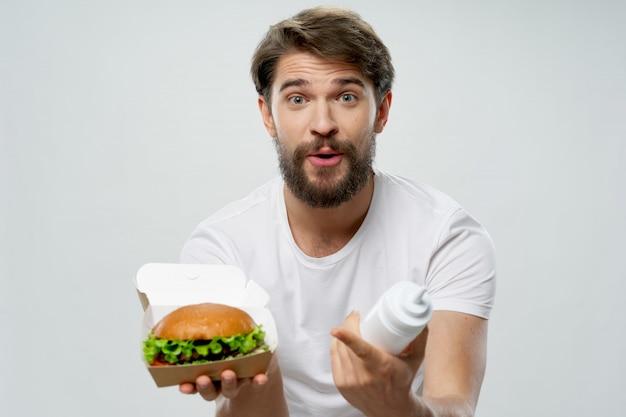 彼の手でジューシーなハンバーガー、ハンバーガーを食べている男と若い男