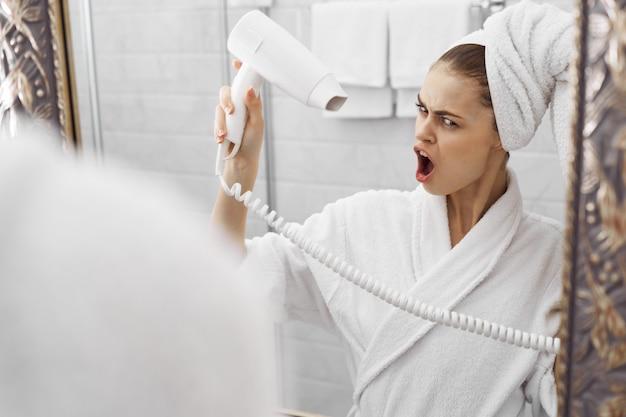 鏡の前でバスローブを着たバスローブを着た女性が顔を見る
