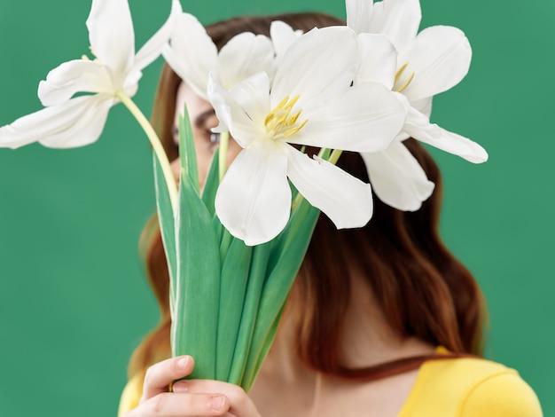 色付きのスペースに花と春の美しい少女、女性が花の花束、女性の日でポーズ