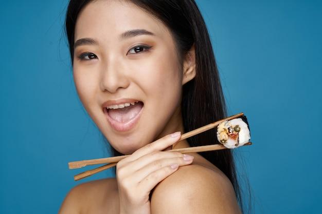 アジアの女性が食品の肖像画、寿司でポーズ
