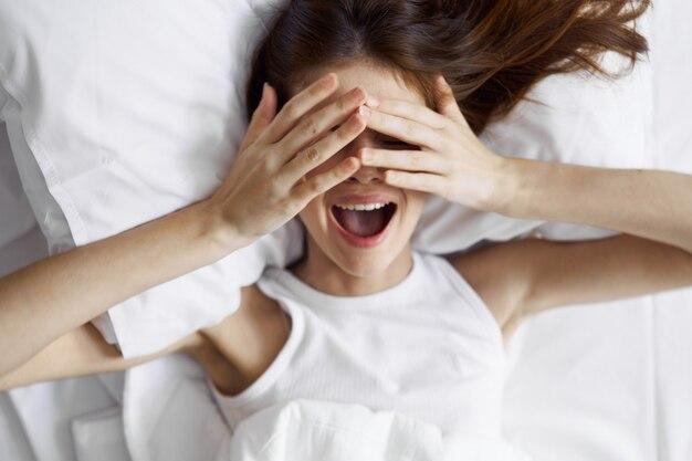 Красивая молодая женщина в своей красивой белоснежной постели расслабляется и расслабляется
