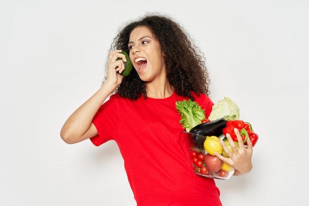 Женщина афроамериканец в пространстве футболки на цветном пространстве позирует