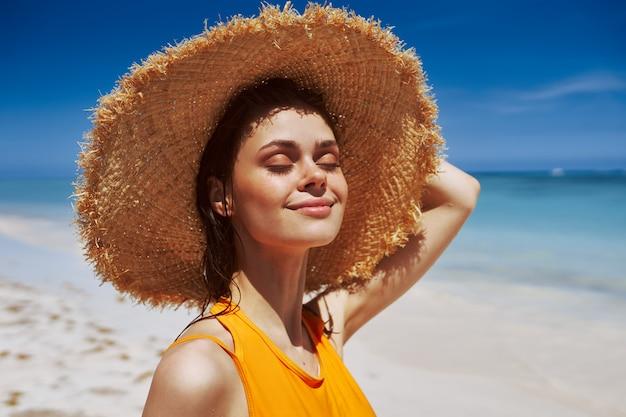 帽子の太陽の下でビーチで女性