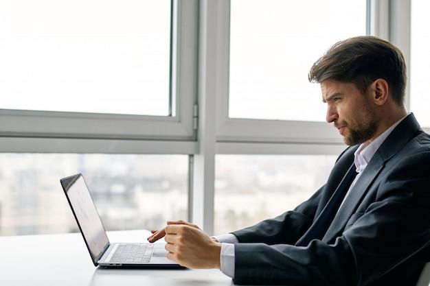 Молодой человек с ноутбуком в деловом костюме работает в пространстве офиса и дома на пространстве окна, проводит онлайн-интервью
