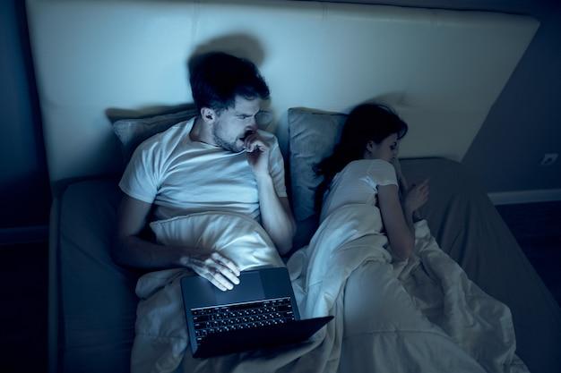 男はベッドの中でノートパソコンで作業し、最愛の女性は眠り、夜間労働、反逆罪