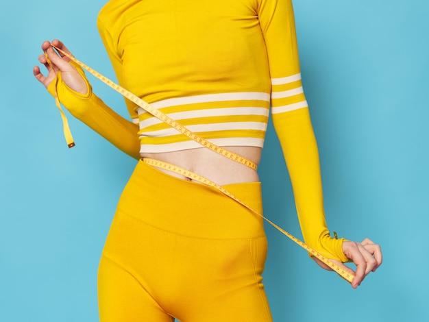 Женщина со стильным спортивным костюмом занимается спортом и делает зарядку, желтый спортивный костюм, синий космос