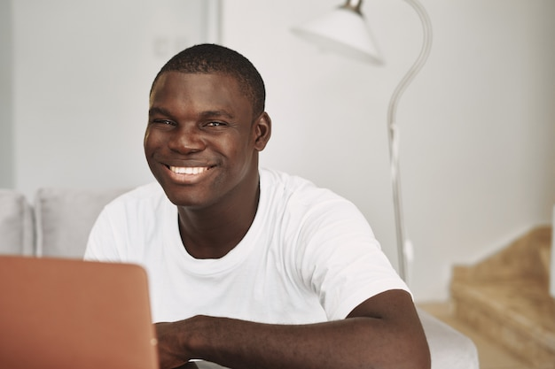 自宅のラップトップを持つ男性のアフリカ系アメリカ人フリーランサー