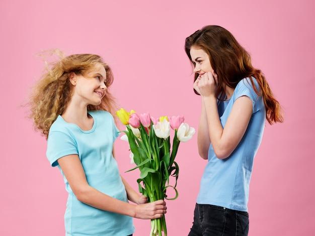 花とスタジオでポーズをとる子供を持つ若い女性