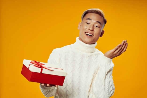 Азиатский мужчина держит подарочную коробку