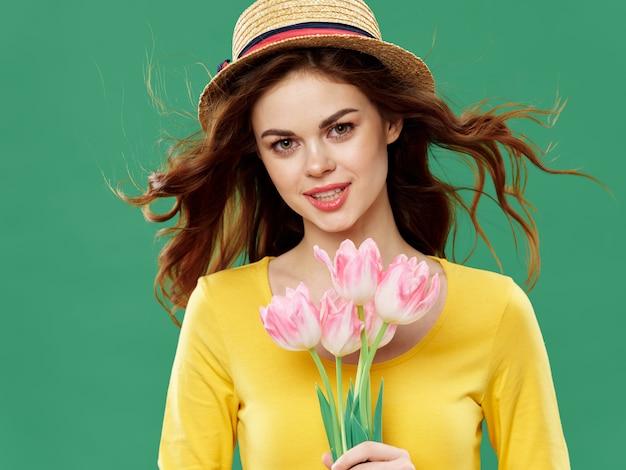 色付きのスタジオに花を持つ春の美しい少女。女性が花束でポーズします。