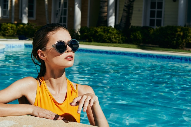 プールで黄色の水着で美しい女性