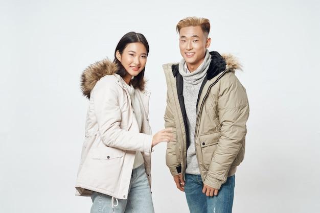 アジアの女性と明るい色のポーズモデルを一緒に男