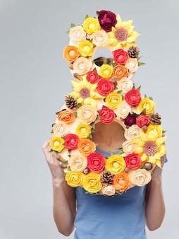 春の色のスタジオの背景に花を持つ美しい少女、女性が花の花束、女性の日でポーズ
