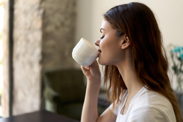 Женщина сидит в кафе, расслабляющий и пить кофе