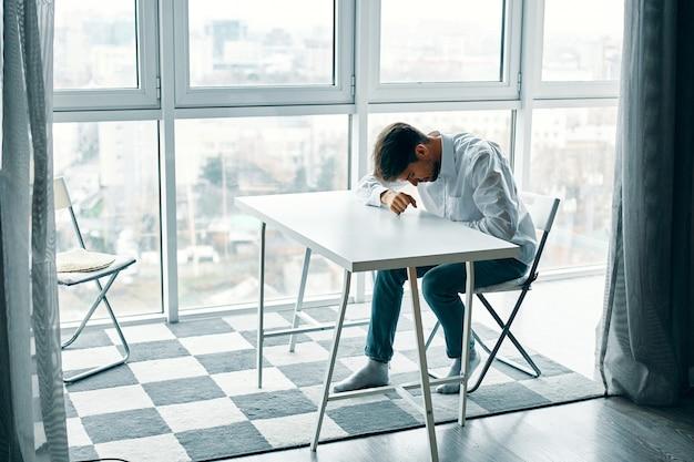 Молодой человек сидит за столом в депрессии на фоне окна