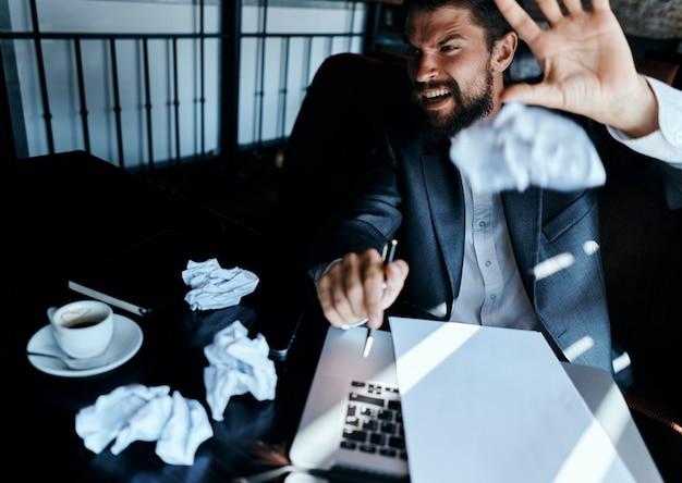 Молодой мужчина бизнесмен сидит за столом с бумагами и пьет кофе, смотрит в окно