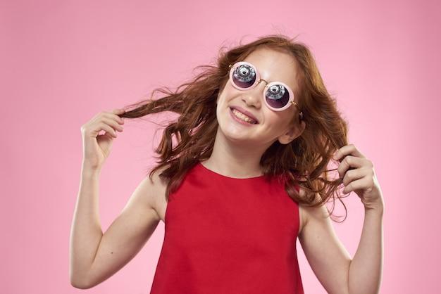 メガネ、ピンクのスペース、美しい笑顔の子でポーズ幸せな少女