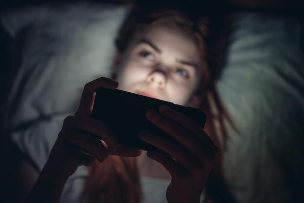 夜の若い女性は彼女の手に電話でベッドにあります。