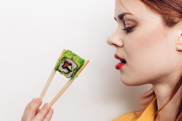 Женщина ест цветные роллы с бамбуковыми палочками, азиатская еда, светлое пространство