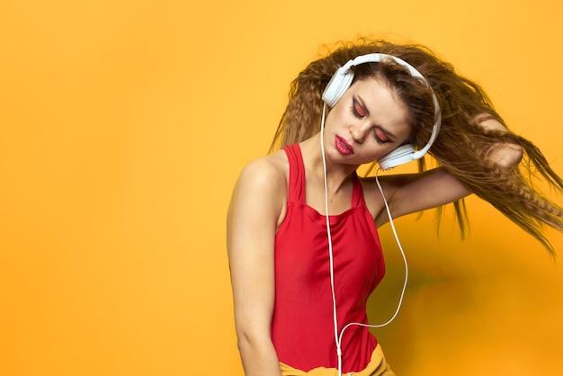 Молодая женщина в наушниках, веселье и смех, купальник вечеринка, желтое пространство