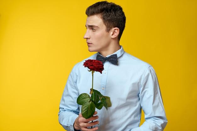 彼の手に美しいバラの花を持つ男